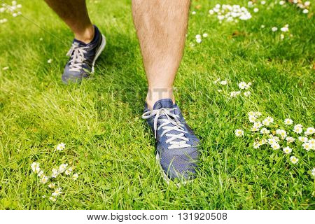 Healthy active lifestyle man athlete with running shoes. Happy sporty runner man with blue sneakers on summer grass in city park getting ready for a fitness jog.