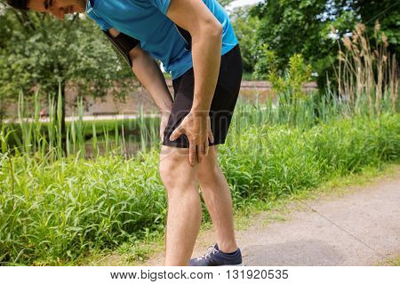 Muscle sports injury. Running muscle strain injury in thigh. Closeup of runner touching leg in muscle pain.
