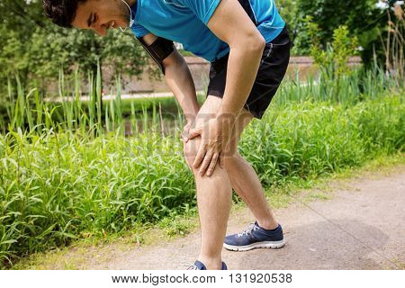 Running injury - Man jogging with knee pain. Close-up view of runner injured jogging in the city park clutching his knee in pain. Male fitness athlete.
