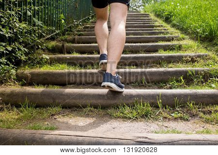 Close up of young man legs running up the stairs in a city park.Runner man Practice training on stairs in a city park.