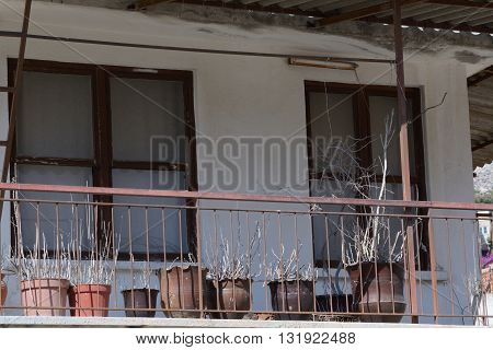 Turkish village house balcony with pots of dried plants
