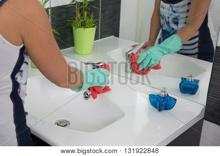 Woman doing chores in bathroom cleaning tap