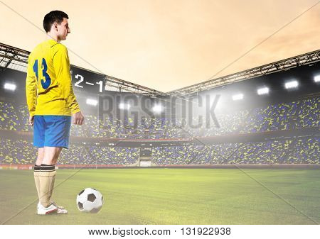 soccer or football player is standing on stadium