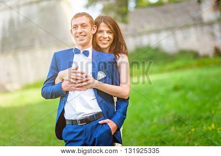 Young couple smiling while waklin in the park in old castle