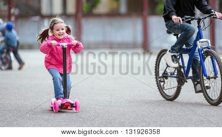 One adorable little girl wearing beautiful clothes riding scooters in a summer city