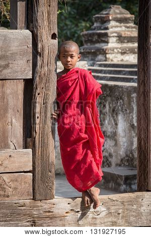 MANDALAY MYANMAR - JANUARY 17 2016 : Young monk standing and looking at Shwenandaw Monastery is built in the traditional Burmese architectural style