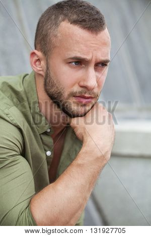 Portrait of a serious man in a green shirt posing on a stone wall background