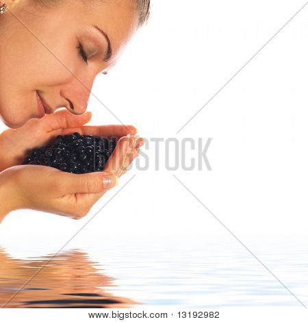 Beautiful girl with a handful of blueberries in rendered water