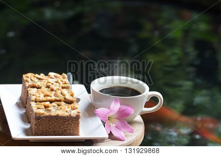 Toffee Cake , Hot Black Coffee And Pink Flowers On A Wooden Table . The Idea Of Refreshing In The Mo