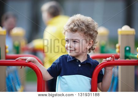 Small curly boy is playing on the playground