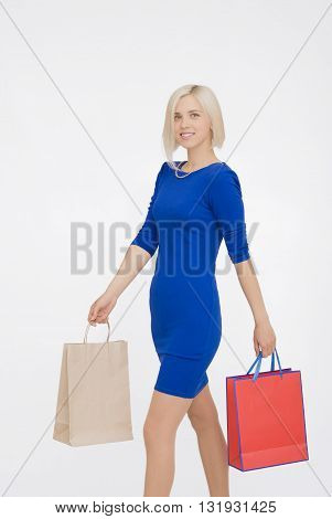 Happy Young Woman with shopping bags in blue dress Isolated On White Background