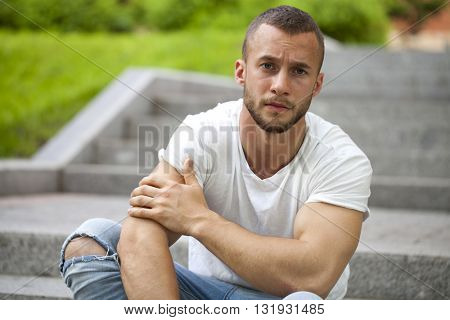 Handsome muscular young man posing on a stone steps background