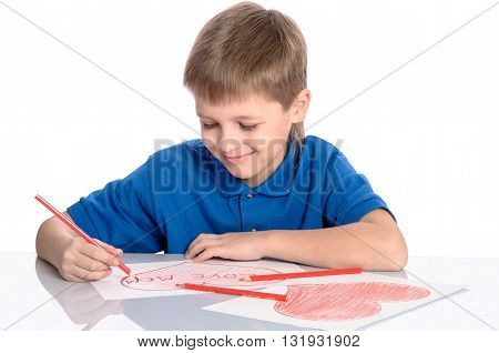 boy drawing a heart that says I love mom