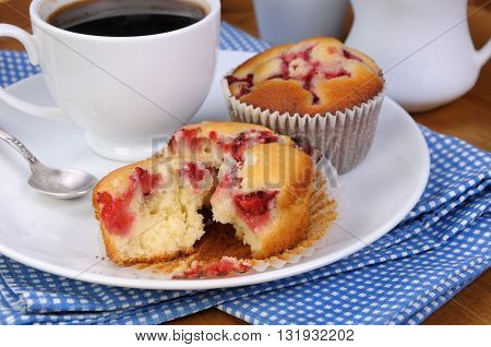 Break muffin with strawberries on a table cup of coffee