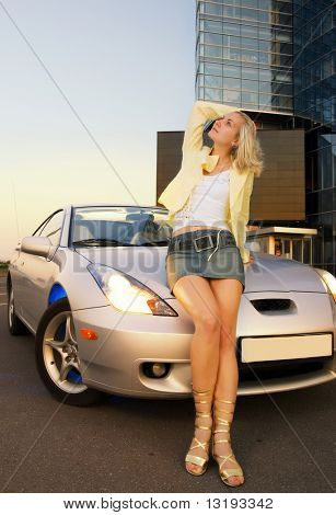 Sexy blond girl sits on modern sport car