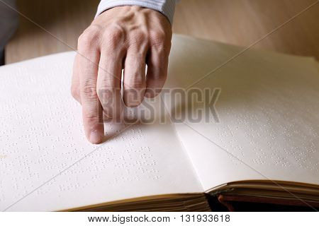 Blind person touching book written in braille writing reading it. Blindness aid visual impairment independent life concept.
