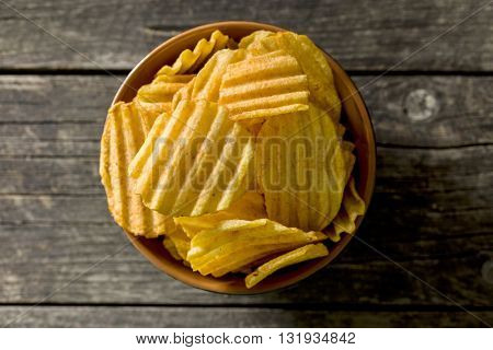 Crinkle cut potato chips on kitchen table. Tasty spicy potato chips in bowl. Top view.