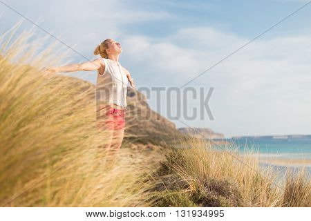 Relaxed woman, arms rised, enjoying sun, freedom and life an a beautiful beach. Young lady feeling free, relaxed and happy. Concept of vacations, freedom, happiness, enjoyment and well being.