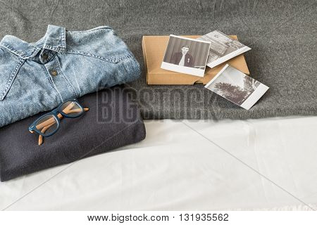 Shot of a bed covered with grey blanket with folded male casual clothes glasses and a box of black and white photographs