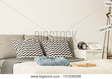 Large bed decorated with patterned pillows in a modern bedroom with white nightstand and personal items