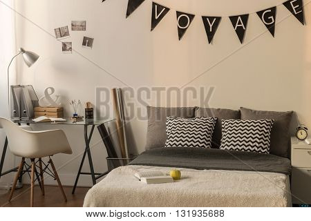Bedroom illuminated with natural afternoon light with a large bed a nightstand and a desk filled with personal items