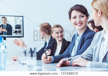 Group of young people on business conference online. Two pretty girls smiling to each other