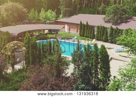 Luxury swimming pool beside the modern hotel and spa resort. Landscape design of resort territory. Beautiful trees and bushes near pool, landscape of park and garden.
