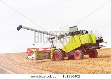 modern combine harvester on stubble field at end of summer.