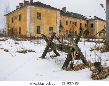 The abandoned two-storey house yellow colored and trestles for sawing firewood on snow