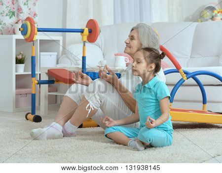 senior woman and  little granddaughter doing exercise home
