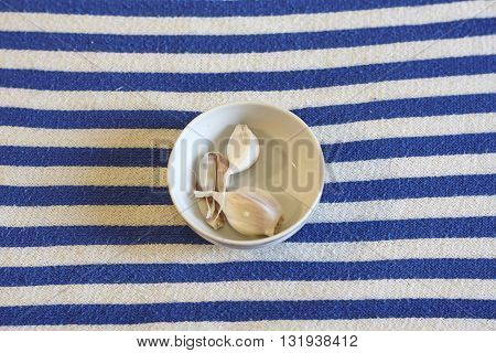 garlic in saucer on white blue textile