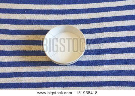 salt in saucer on white blue textile