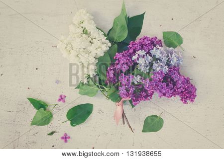 Posy of fresh lilac flowers on white wooden table, retro toned