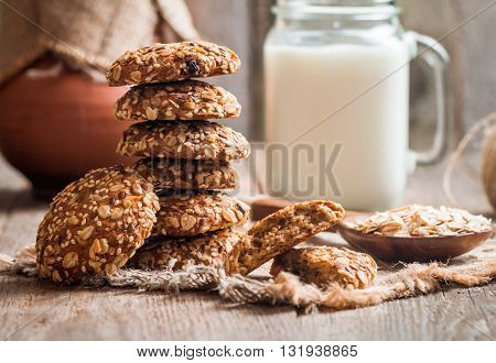 Oatmeal cookies with milk on burlap and rustic wooden table