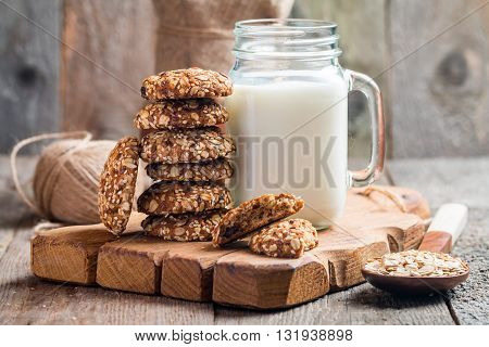Oatmeal cookies with milk on cutting board on rustic wooden table