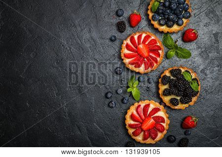 Tarts with lemon cream and fresh berries on black background, top view