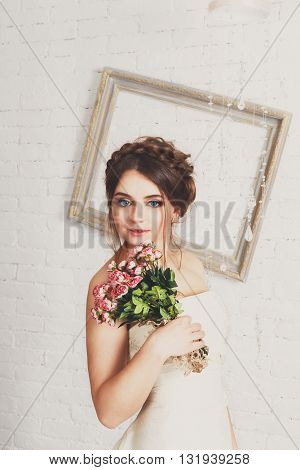 Wedding dress fashion. Beautiful young bride portrait in vintage, shabby chic wedding dress with bridal bouquet. Girl model in champaigne color rustic dress, studio shot, high key