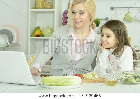 portrait of happy mother and daughter cooking  in kitchen  with laptop