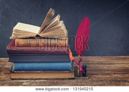 Wooden bookshelf with pile of antique books and red feather pen, retro toned