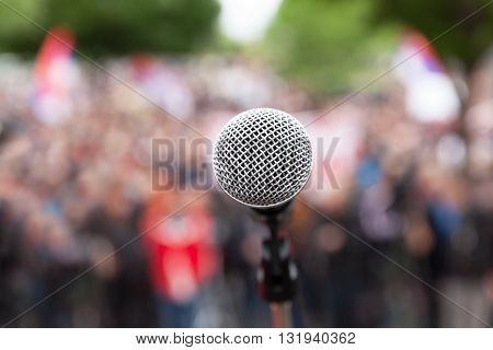 Microphone in focus against blurred audience. Political rally.