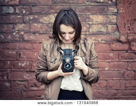 Pretty young woman holding retro camera and taking photo on vintage brick wall background. Selective focus on camera. Toned photo with copy space. Vintage style photo.