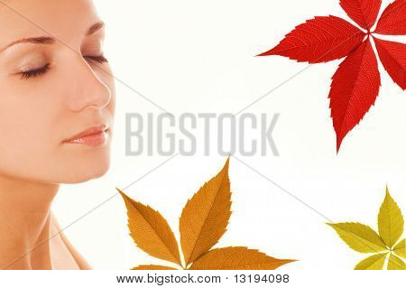 Beautiful girl's face and colorful autumn leaves around her