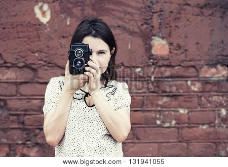 Girl holding retro camera and taking photo on vintage brick wall background. Selective focus on camera and hands of model. Toned photo with copy space. Vintage style photo.