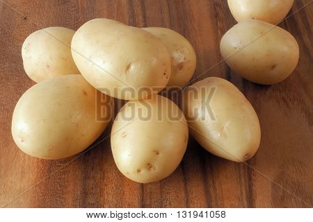 A collection of small pale skinned washed potatoes on a dark colored wooden cutting board.