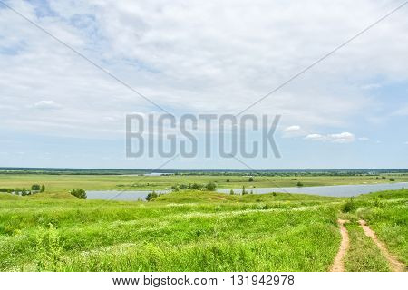 Landscape with footpath to the river through a green field on a background of blue sky with white clouds on a summer day