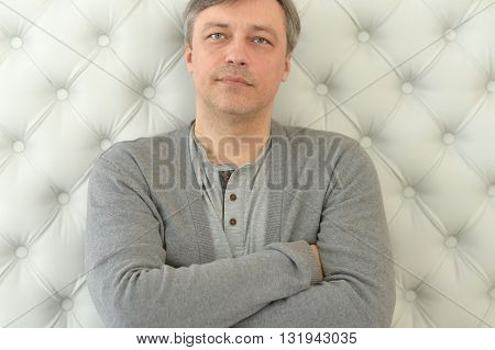 Handsome attractive mature man with arms crossed looking at camera