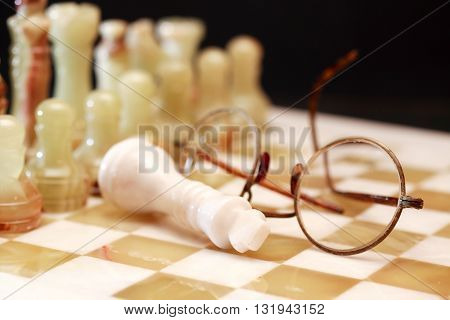 Set of chess pieces made from Onyx on board near spectacles against dark background
