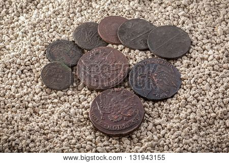 Copper Russian coins of 18-19 centuries in a patina and oxides on white coarse sand.