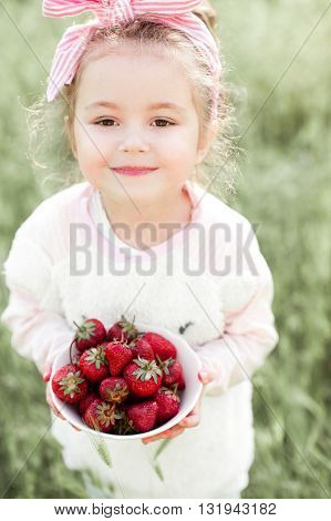 Smiling baby girl 4-5 year old holding bowl with strawberry outdoors. Looking at camera. Childhood.