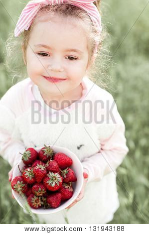 Cute kid girl 4-5 year old eating strawberry outdoors. Childhood.